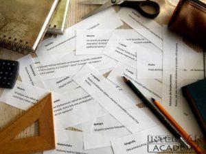 kartki z pytaniami na stole wśród przyrządów szkolnych