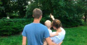 Mężczyzna i kobieta z małym dzieckiem. Kobieta trzyma dziecko na jednej ręce a drugą pokazuje dziecku coś na drzewie. Zdjęcie zrobione w terenie zielonym. Wszystkie postaci w ujęciu od tyłu.